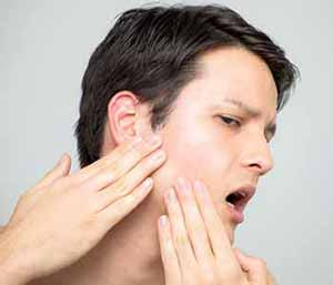 Image of a man suffering from TMJ pain
